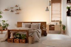 Letto matrimoniale semplice, tavola, scatole con le piante, ciechi di finestra dopo fotografia stock libera da diritti