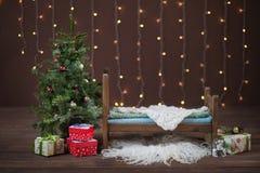 Letto neonato su un fondo marrone con le luci del nuovo anno e la decorazione di Natale con i regali fotografia stock