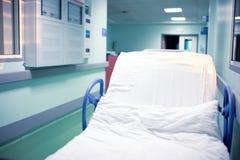 Letto a ruote vuoto nel corridoio dell'ospedale vicino alla reception fotografia stock