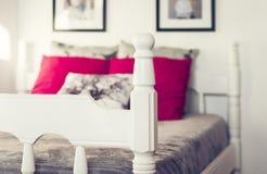Letto scolpito di legno bianco con il copriletto grigio ed i cuscini rossi fotografia stock libera da diritti