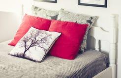 Letto scolpito di legno bianco con il copriletto grigio ed i cuscini rossi fotografie stock