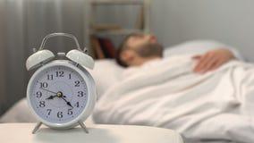 Letto vicino dell'uomo di sonno dell'orologio bianco, abitudine sana di mattina, bioritmi, jet lag stock footage