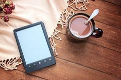 Lettore del libro elettronico e tazza di cacao su un fondo di legno Fotografia Stock