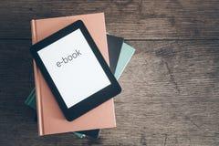Lettore del libro elettronico su una pila di libri fotografie stock