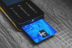 Lettore della carta di credito con una carta di credito blu inserita immagini stock libere da diritti