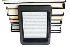Lettore di Ebook sui libri del mucchio Immagine Stock Libera da Diritti
