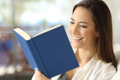 Lettore felice che legge un libro a casa Fotografia Stock Libera da Diritti