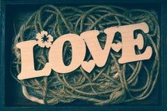 Lettrage décoratif - aimez, découpé hors du bois sur une corde dans la boîte Images stock