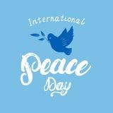 Lettrage de calligraphie écrit par main internationale de jour de paix sur le fond bleu Photographie stock libre de droits