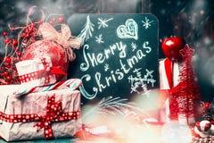 Lettrage de carte de Joyeux Noël dessiné sur le tableau arrière avec le cadeau fait main avec la décoration rouge de vacances Photographie stock libre de droits