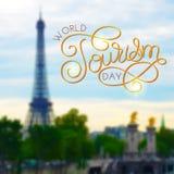 Lettrage de main de jour de tourisme du monde sur le fond brouillé de photo Image libre de droits