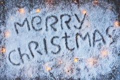 Lettrage tiré par la main de Joyeux Noël avec des lumières au-dessus du conseil en bois Photos stock