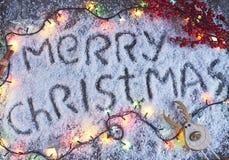 Lettrage tiré par la main de Joyeux Noël avec des lumières au-dessus du conseil en bois Photographie stock