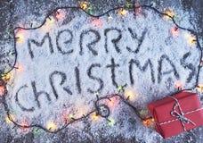 Lettrage tiré par la main de Joyeux Noël avec des lumières au-dessus du conseil en bois Photo stock