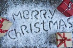 Lettrage tiré par la main de Joyeux Noël avec le boîte-cadeau au-dessus de b en bois Photos stock