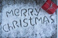 Lettrage tiré par la main de Joyeux Noël avec le boîte-cadeau au-dessus de b en bois Images libres de droits