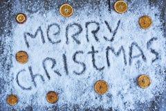 Lettrage tiré par la main de Joyeux Noël avec le fruit orange au-dessus du bois Images libres de droits
