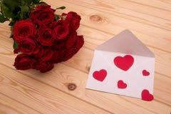 Lettre avec des coeurs et un bouquet des roses rouges sur le backgrou en bois Photos libres de droits