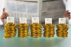 Lettre COURANTE sur la pile de pièces d'or Photographie stock