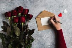 Lettre d'amour d'écriture de stylo de participation de main de femme de jour de valentines avec la carte de voeux Photographie stock
