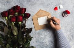 Lettre d'amour d'écriture de stylo de participation de main d'homme de jour de valentines avec la carte de voeux Photo libre de droits