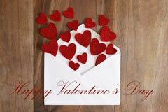 Lettre d'amour de jour du ` s de Valentine renversant les coeurs rouges sur le Ba en bois Photographie stock