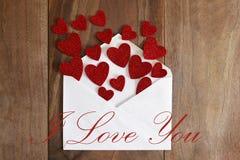 Lettre d'amour de jour du ` s de Valentine renversant les coeurs rouges sur le Ba en bois Photos stock