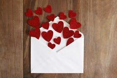 Lettre d'amour de jour du ` s de Valentine renversant les coeurs rouges sur le Ba en bois Image stock