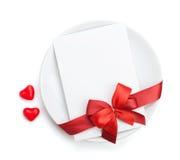 Lettre d'amour de Saint-Valentin au-dessus de plat avec l'arc rouge Photographie stock libre de droits