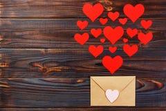 Lettre d'amour de Valentine Day L'enveloppe du papier de métier avec les coeurs rouges amassent la diffusion sur le fond en bois  Photos stock