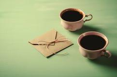 Lettre d'amour, enveloppe et deux tasses de café roses Carte de Valentines Configuration horizontale et plate Photographie stock libre de droits
