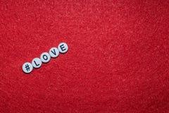 Lettre d'amour sur un fond rouge, lettres sous forme de boutons en plastique avec un hashtag de signe Image libre de droits