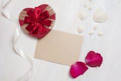 Lettre de maquette avec un cadeau sous forme de coeur et pétales des roses carte de voeux pour le jour de valentines avec l'endro Photographie stock