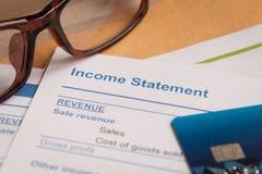 Lettre de rapport des revenus de résultats sur l'enveloppe et le monocle bruns, affaires Photos stock