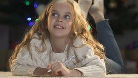 Lettre enthousiaste d'écriture de fille à Santa Claus rêvant de la pile de cadeaux, enfance banque de vidéos
