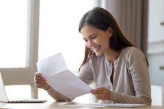 Lettre enthousiaste heureuse de lecture de femme avec de bonnes nouvelles, grande offre image stock