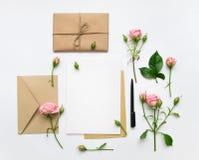 Lettre, enveloppe et cadeau sur le fond blanc Cartes d'invitation, ou lettre d'amour avec les roses roses Concept de vacances, vu Photographie stock libre de droits