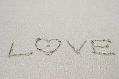 Lettre et boucle d'amour sur le sable Photographie stock