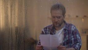 Lettre heureuse de lecture d'homme de fenêtre pluvieuse derrière aimée, relations de distance banque de vidéos