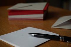 Lettre noire d'annonce d'écriture de stylo avec l'enveloppe sur le bureau en bois Images stock