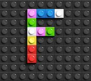 Lettres colorées F d'alphabet des briques de lego de bâtiment sur le fond noir de brique de lego Fond de Lego lettres 3D illustration libre de droits
