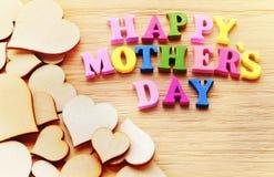 Lettres colorées heureuses de jour de mères orthographiant la salutation sur la table en bois Images libres de droits