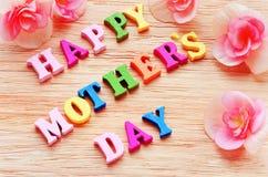 Lettres colorées heureuses de jour de mères orthographiant la salutation sur la table en bois Photos stock