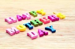 Lettres colorées heureuses de jour de mères orthographiant la salutation sur la table en bois Photographie stock