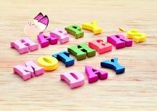 Lettres colorées heureuses de jour de mères orthographiant la salutation sur la table en bois Photographie stock libre de droits