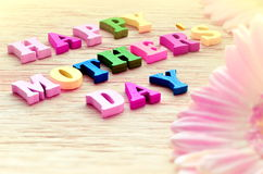 Lettres colorées heureuses de jour de mères orthographiant la salutation sur la table en bois Photo stock