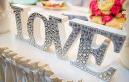 Lettres décoratives formant l'amour de mot avec des wildflowers Images stock