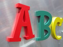 Lettres d'alphabet de couleur sur le métal argenté, Photos stock