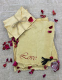 Lettres d'amour antiques de papier parcheminé avec les pétales de rose et la bouteille de parfum Image stock