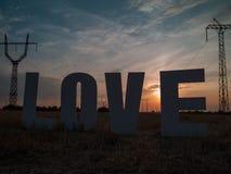 Lettres d'amour de photo sur le fond de coucher du soleil Images stock